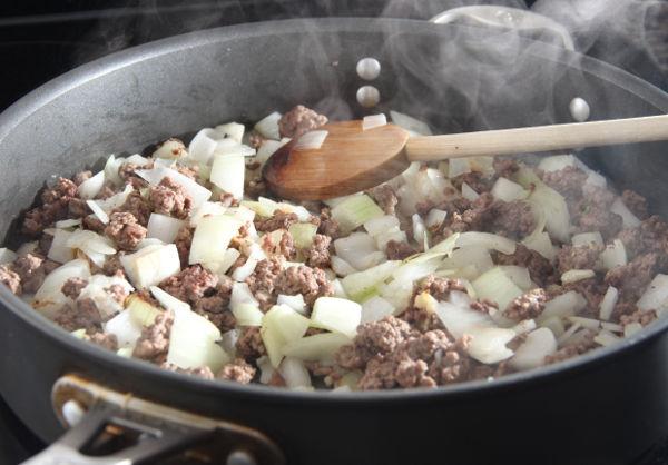 """<p style=""""text-align: justify;"""">Обжарить на сковороде репчатый лук, нарезанный мелкими кубиками, и добавить к нему фарш. Лучше всего подходит телятина, говядина или нежирная баранина. Посыпать черным молотым перцем и зирой, которую мясо очень любит. Мелко порубить чеснок и жгучий перец, добавить к фаршу, перемешать и продолжать обжаривать.</p> <p style=""""text-align: justify;"""">Положить в фарш помидоры, нарезанные кубиками. Завершающим штрихом станет добавление мелкорубленой зелени. Сковороду закрыть крышкой и, потушив еще 7 минут, выключить плиту.</p>"""