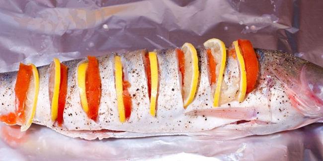 <p>Кружочки помидора вставить в надрезы. Часть лука и оставшиеся помидоры отправить внутрь судака.</p>
